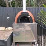 A wood fired oven on a stainless steel base that's been fitted with wheels