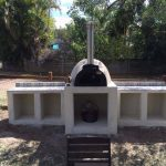 A wood fired oven sitting on a large concrete base with plenty of room to store firewood