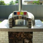 A decorated wood fired oven sites on a tile base built on brick supports