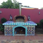 A highly decorated base is supporting a wood fired oven from Sydney Wood Fire Ovens