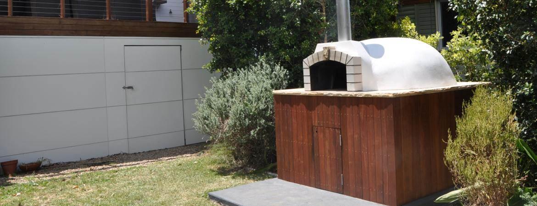 A wood fired oven set amongst garden shrubbery